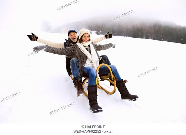 Senior couple having fun with sledge walking in the snow
