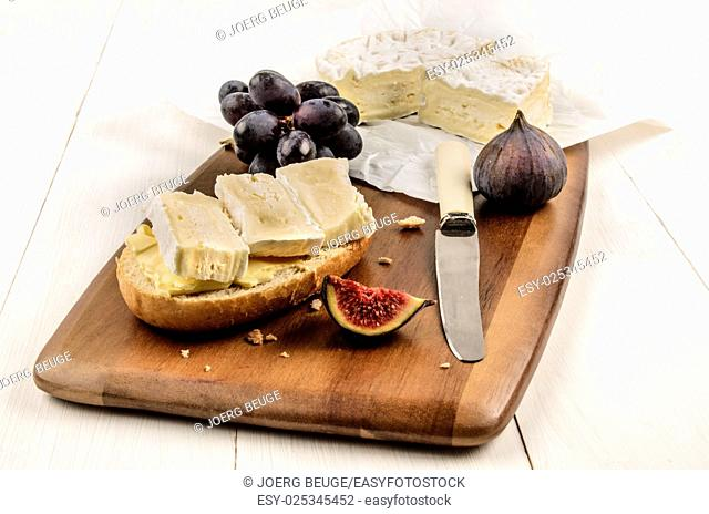 half bread roll with camembert on a wooden board, also with a fig and red grapes