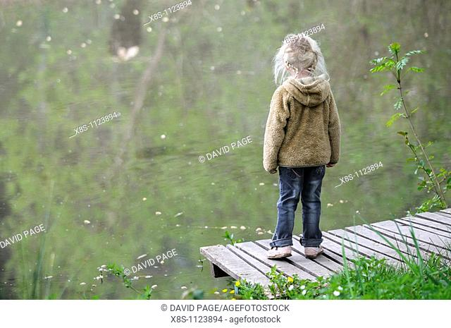 Four year old girl standing on her own by the side of a pond