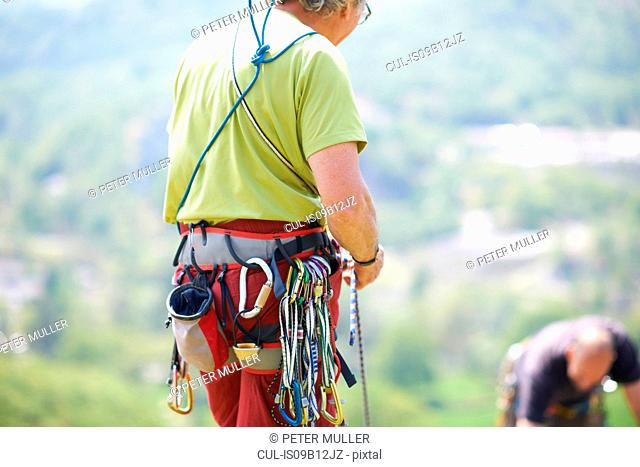 Rear view of rock climber wearing safety harness