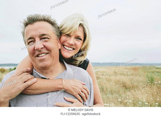 Happy senior couple embracing on a grassy beach; Coquitlam, British Columbia, Canada