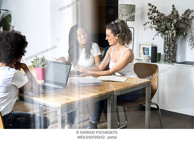 Three women with laptop and documents talking at table