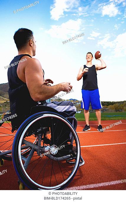 Paraplegic athlete in wheelchair tossing ball with friend
