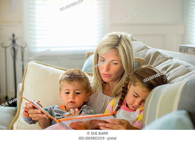 Mid adult woman reading with daughter and toddler son on sofa