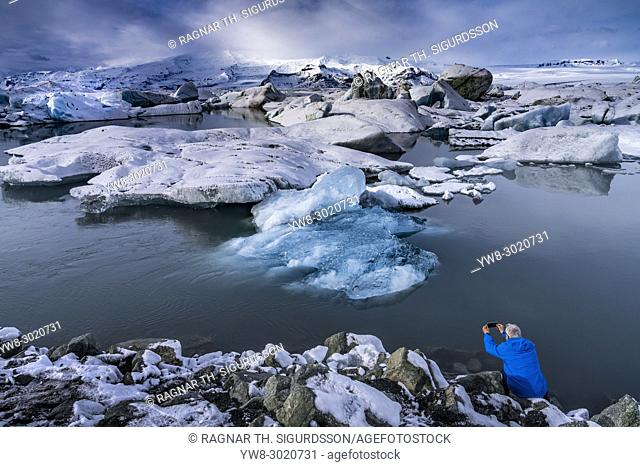 Tourist taking pictures, Jokulsarlon Glacial Lagoon, Iceland