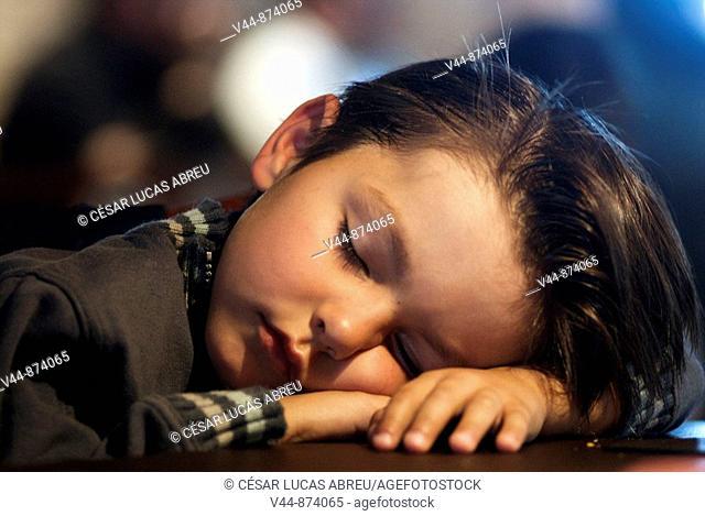 5 years old boy sleeping in a restaurant