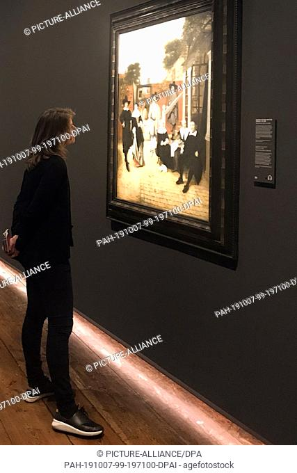 """07 October 2019, Netherlands, Delft: A woman is looking at the painting """"""""Portrait of a Delft Family"""""""" (1657-1660) by the Dutch painter Pieter de Hooch at the..."""
