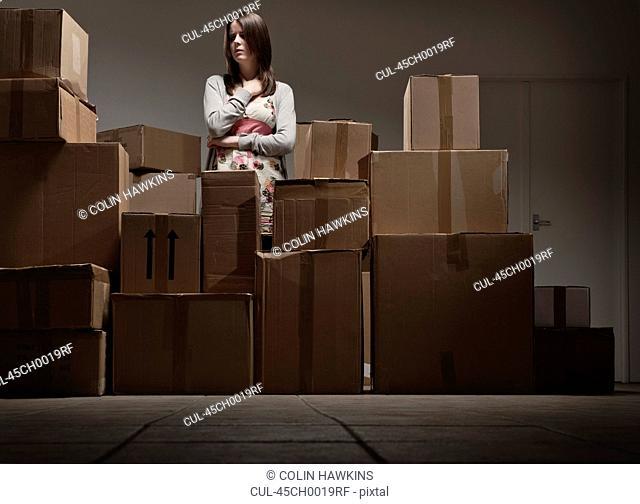 Teenage girl in pile of cardboard boxes