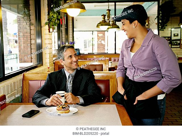 Hispanic waitress talking to businessman in restaurant