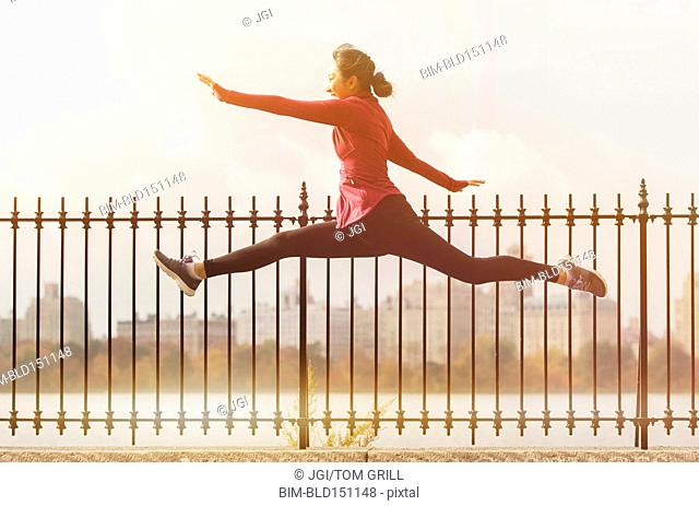 Asian woman leaping on waterfront path