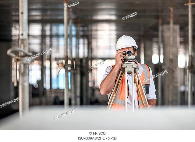 Mid adult male surveyor looking through theodolite on construction site