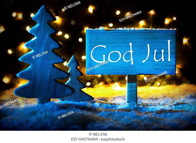 Sign With Swedish Text God Jul Means Merry Christmas. Blue Christmas Tree With Snow And Magic Glowing Lights In Backround. Card For Seasons Greetings