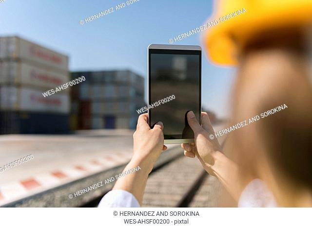 Close-up of female worker holding tablet on railway near to cargo containers on industrial site