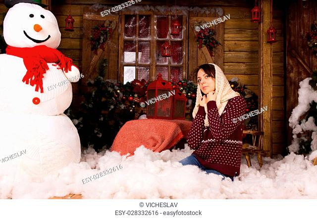 Young Woman Kneeling on the Floor Wearing Trendy Winter Fashion with Scarf on he Head, with Cottons Near Large Snow Man and Other Christmas Decorations