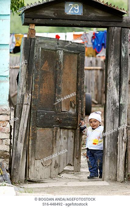 Happy child opening the gate of his yard - Tigmandru village, Mures County, Transylvania, Romania
