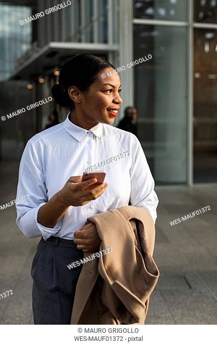 Portrait of smiling businesswoman with cell phone