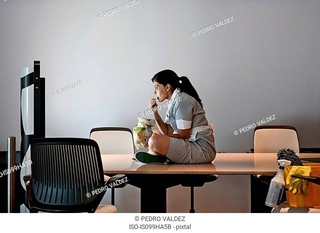 Office cleaner watching screen in conference room