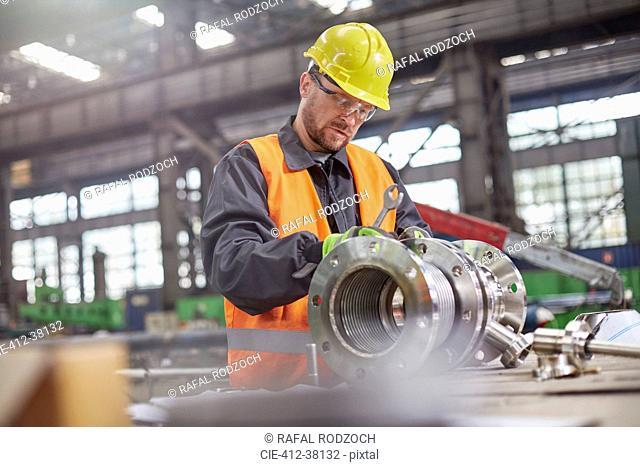 Male worker assembling steel part in factory