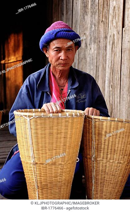 Karen hill tribe man with baskets sitting in front of his house in north Thailand, Asia