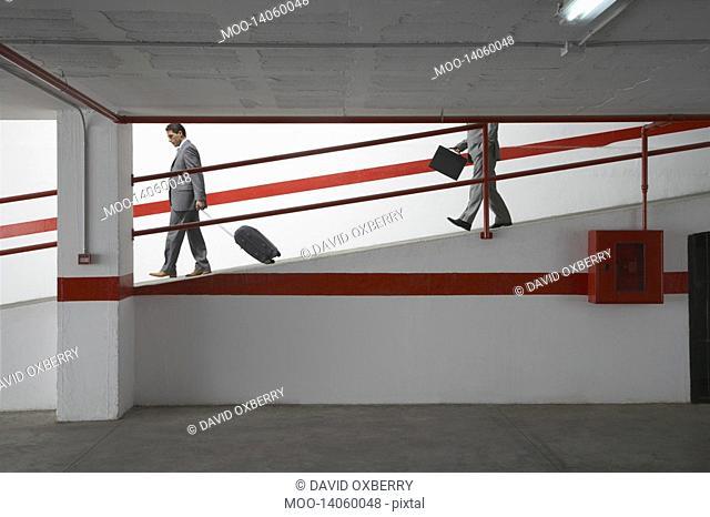 Two businessmen walking down ramp in parking garage with luggage
