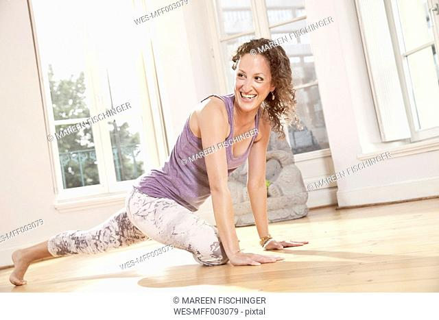 Happy woman getting into yoga pose in sunny studio