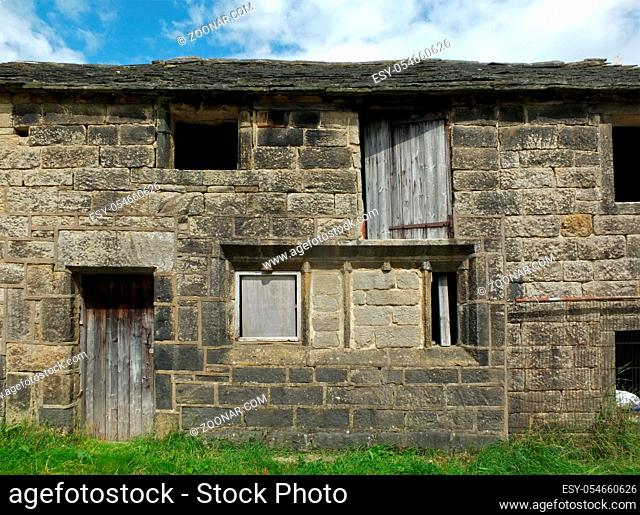 ancient abandoned stone cottage in a row of rural buildings with empty windows and wooden doors with the pavement overgrown with grass
