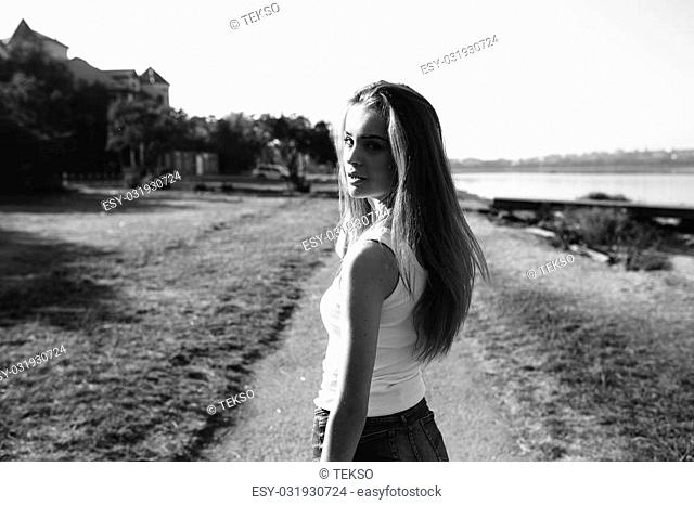 Photo of a beautiful young girl on the sidewalk near the beach