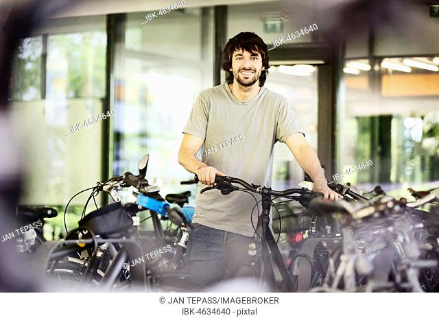 Young man, student, parks his bicycle, University, Aachen, North Rhine-Westphalia, Germany