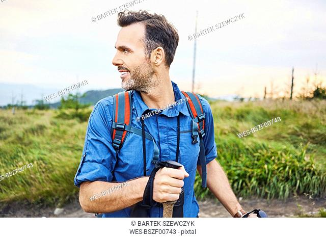 Smiling man hiking in the mountains turning round