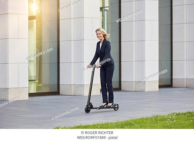 Businesswoman on e-scooter passing office building in the city