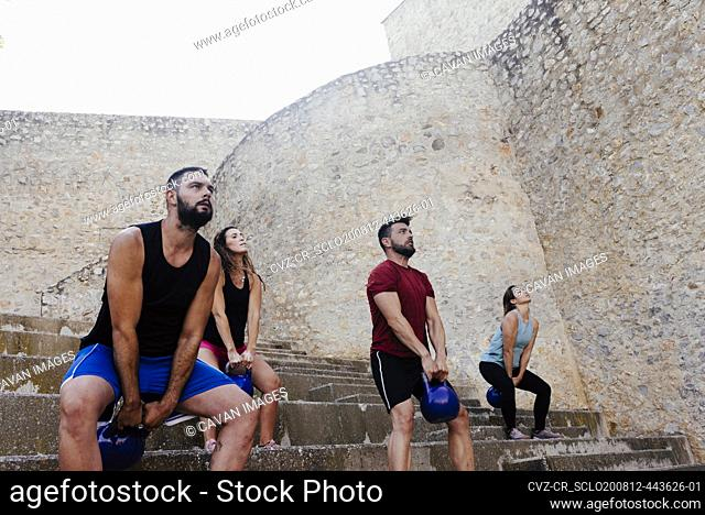 Athletes lifting a kettelbell crossfit weights in an urban enviroment