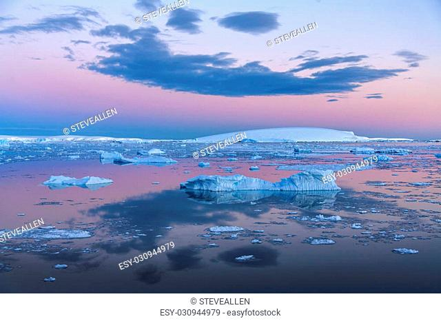 The Midnight sun over the icebergs in the Weddell Sea near the Antarctic Peninsula in Antarctica