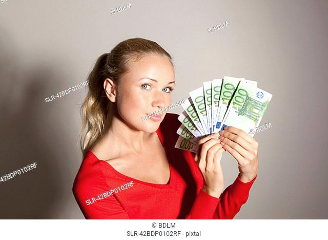Woman holding stack of Euros