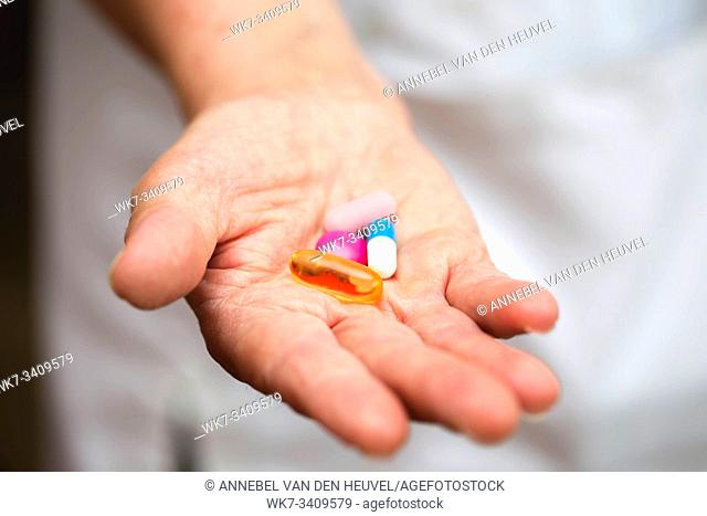 Many multi-colored pills in a Senior's hands. Painful old age. Caring for the health of the elderly nurse