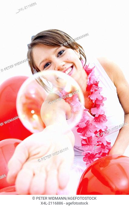 Young woman with flower necklace and soap bubbles (model-released)