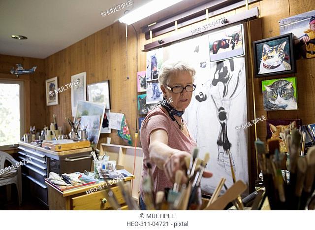 Senior woman artist painting in art studio