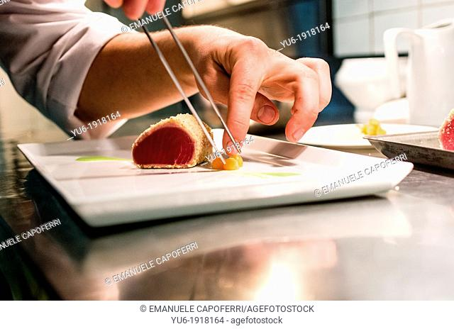 Hand of chef prepares a dish