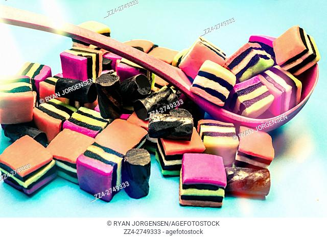 Pile of black liquorice allsorts and square colorful lolly chunks placed in ladle against light blue background