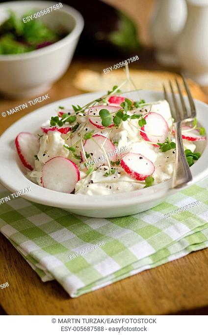 Summer potato salad topped with radish and cress