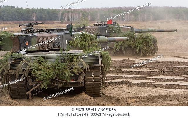 12 December 2018, Mecklenburg-Western Pomerania, Torgelow: Leopard 2 main battle tanks drive on the Jägerbrück military training area