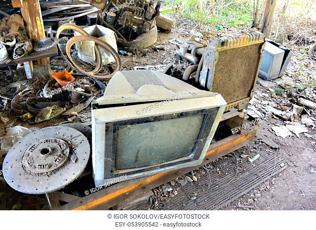 broken TVs and machine parts are lying on a wooden pallet in the dust and dirt on the side of the road in cambodia