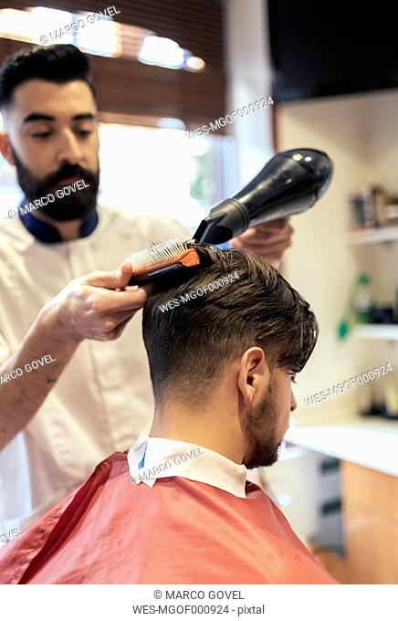 Barber blow-drying and brushing hair of a customer