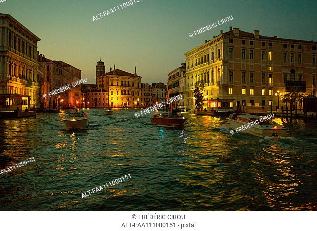Boats travel on the Grand Canal in Venice, Italy, at dusk
