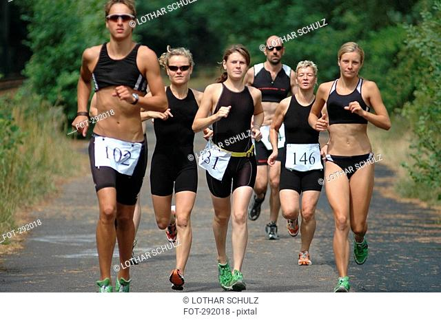 Group of people running on road in sports race