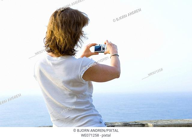 Woman using digital camera above the sea