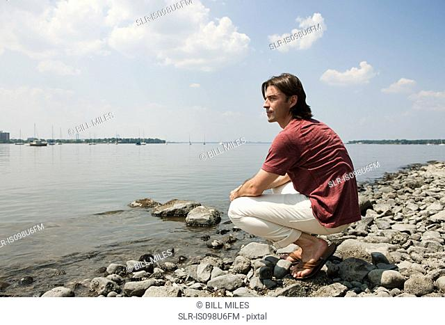 Mid adult man crouching on beach looking at view