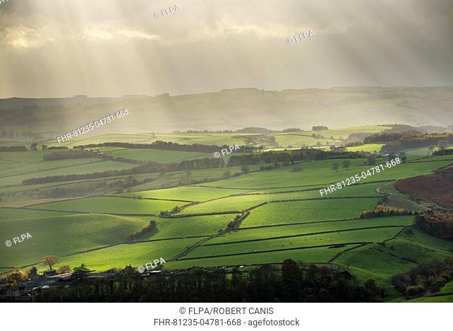 Sunbeams illuminating fields in rural landscape, near Baslow, seen from Baslow Edge, Peak District, Derbyshire, England, November