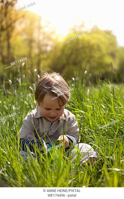 Boy sitting in green grass looking down (easter eggs). Hennef-Lichtenberg, Germany