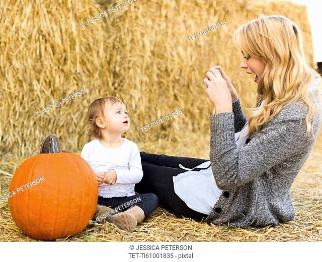 Mother photographing daughter (12-17 months) with large pumpkin