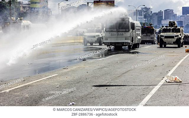 Protesters take cover from the riot police water cannon during a march towards the Ombudsman's Office in protest of President Nicolas Maduro in Caracas